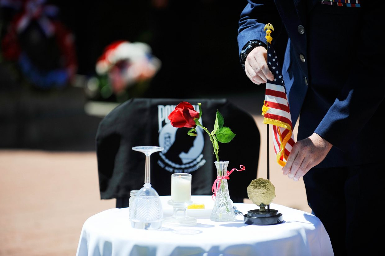 A flag is placed at a table recognizing prisoners of war and those missing in action during Monday's Memorial Day ceremony at Steamboat Springs Cemetery.