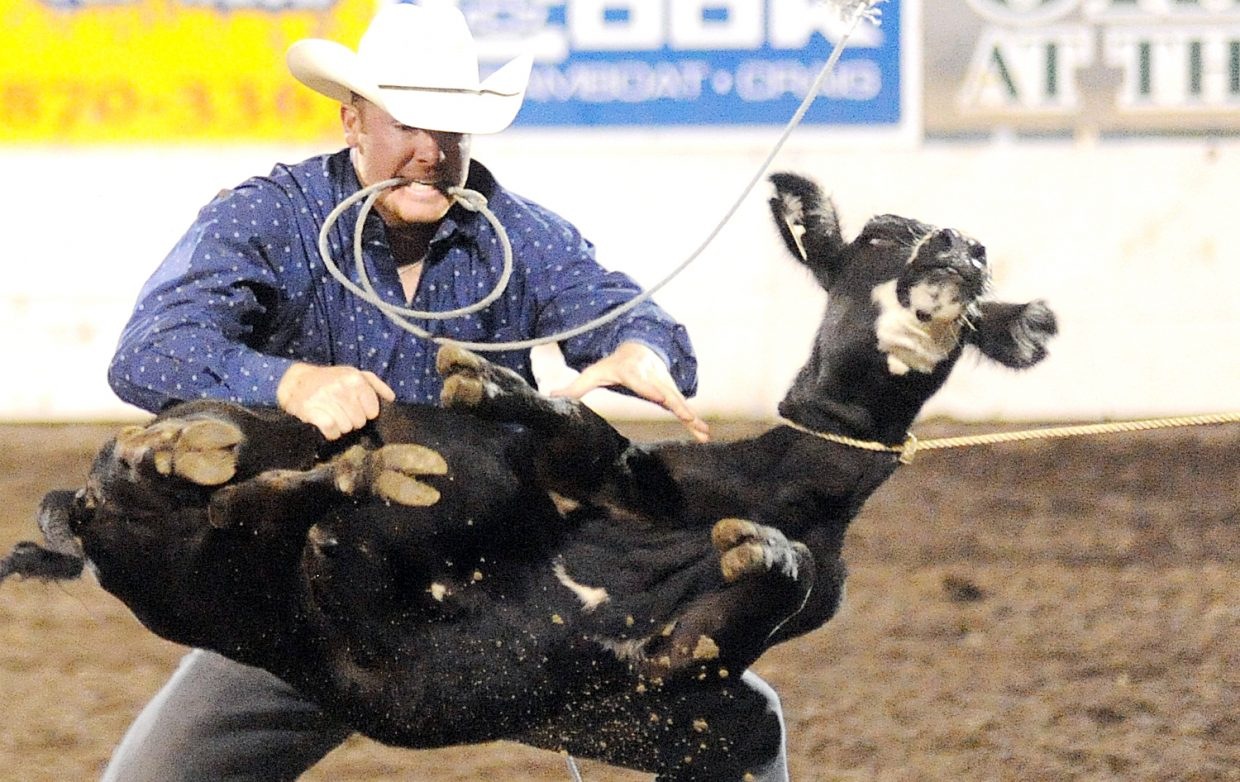 Jon Peek flips his calf to try for a quick tie job during the tie-down roping event Saturday at the Steamboat Springs Pro Rodeo Series.