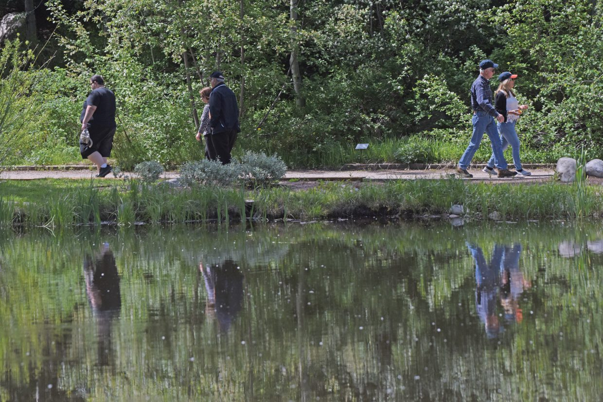 Visitors stroll through the Yampa River Botanic Park Thursday afternoon.  The park opened up about three weeks earlier than normal this year, and the flower beds and trees are in top early-season shape.