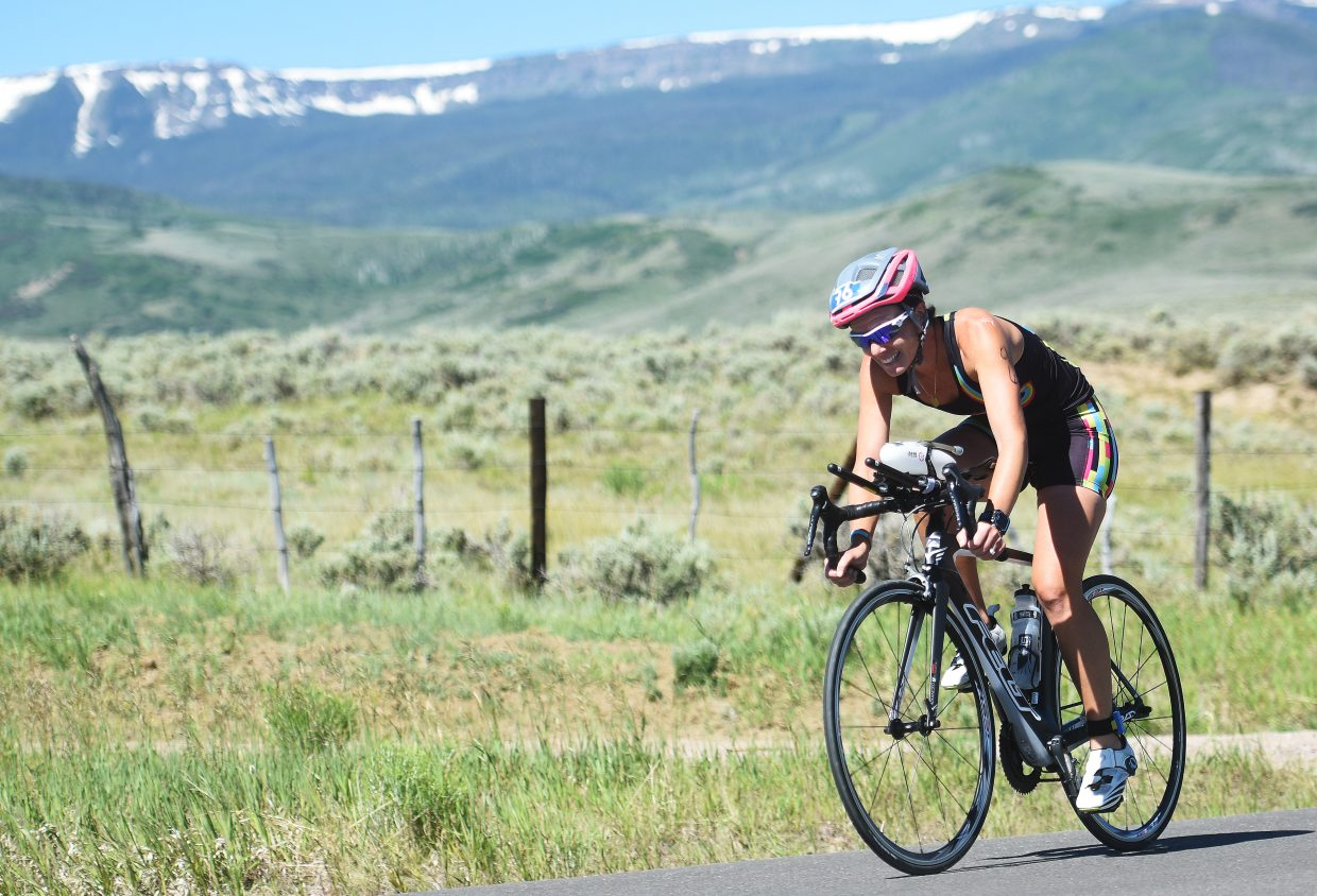 The Flat Tops Wilderness Area looms behind an athlete Sunday during the Tri the Boat half-Ironman triathlon.