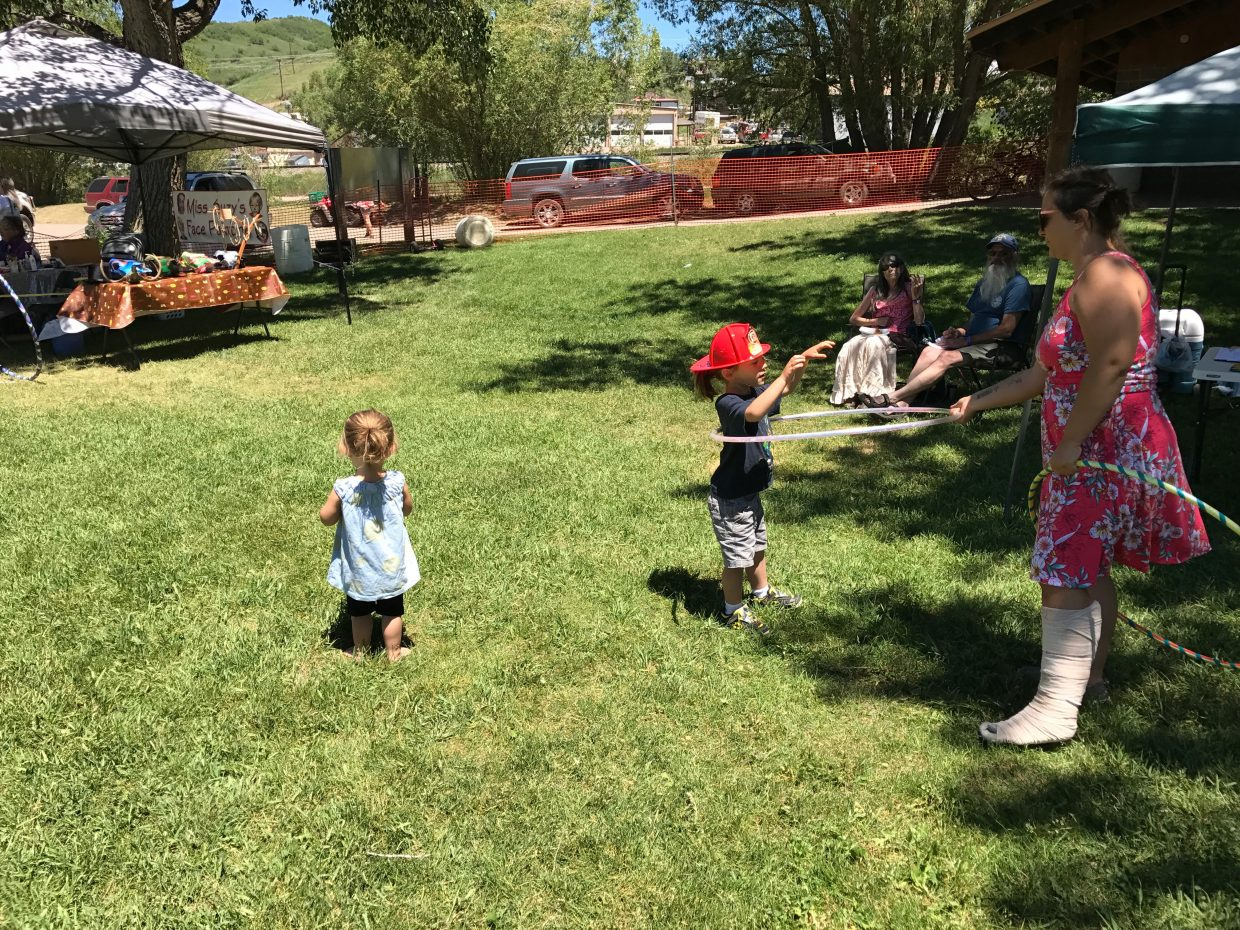 Kayla Sprowls, right, shows her daughters Ollie, center, and Ila the finer points of hula-hooping.