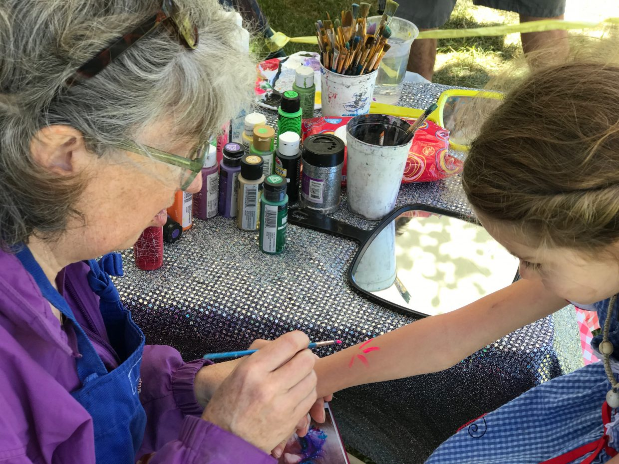Miss Suzy, right, paints a floral design on the arm of Talayeh Baughman Saturday at Taste of South Routt in Oak Creek.