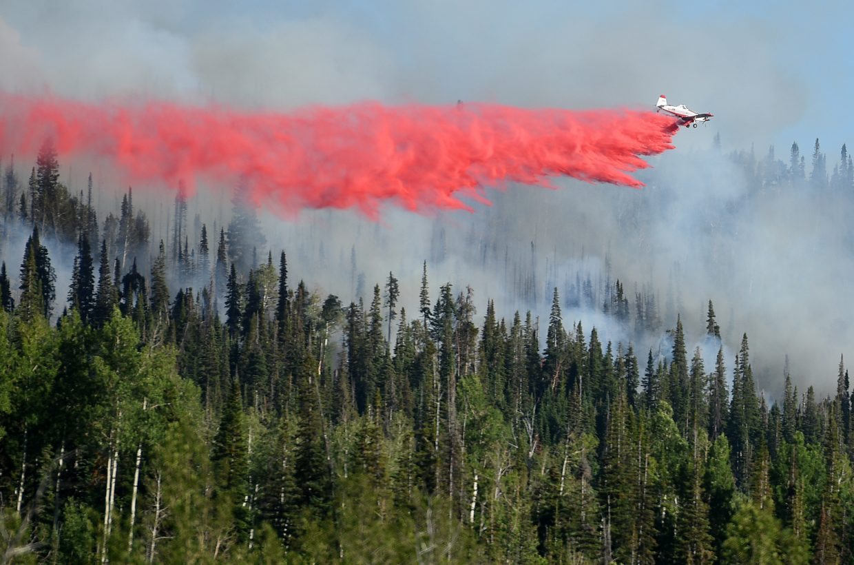 A plane skims above the forest on Saturday to dump fire retardant around the Mill Creek fire in North Routt County.