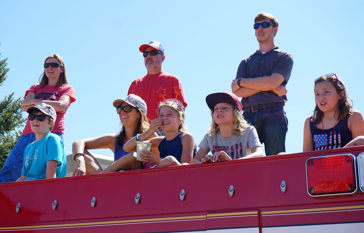 Spectators watch the Fourth of July parade from the top of a fire engine in downtown Steamboat Springs.
