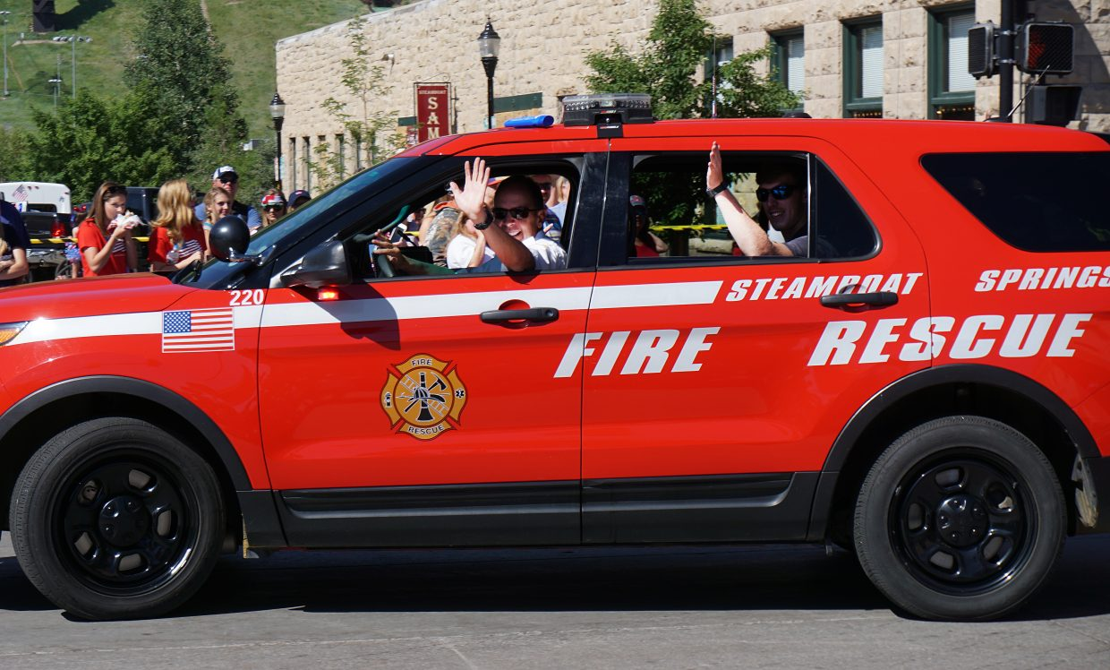 Steamboat Springs Fire Rescue Chief Mel Stewart waves to the crowd during the Fourth of July parade in downtown Steamboat.
