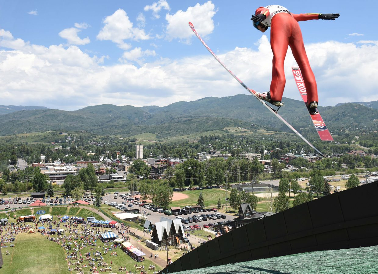 A ski jumper takes flight over a huge crowd during the 2017 Fourth of July ski jumping competition.