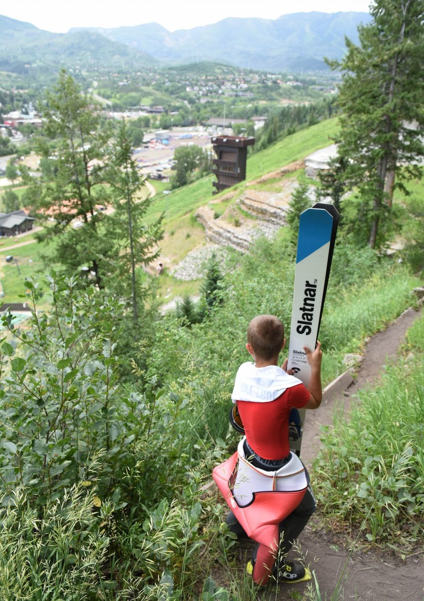 A young skier looks back toward town while hiking up to the HS75 ski jump in Steamboat Springs.