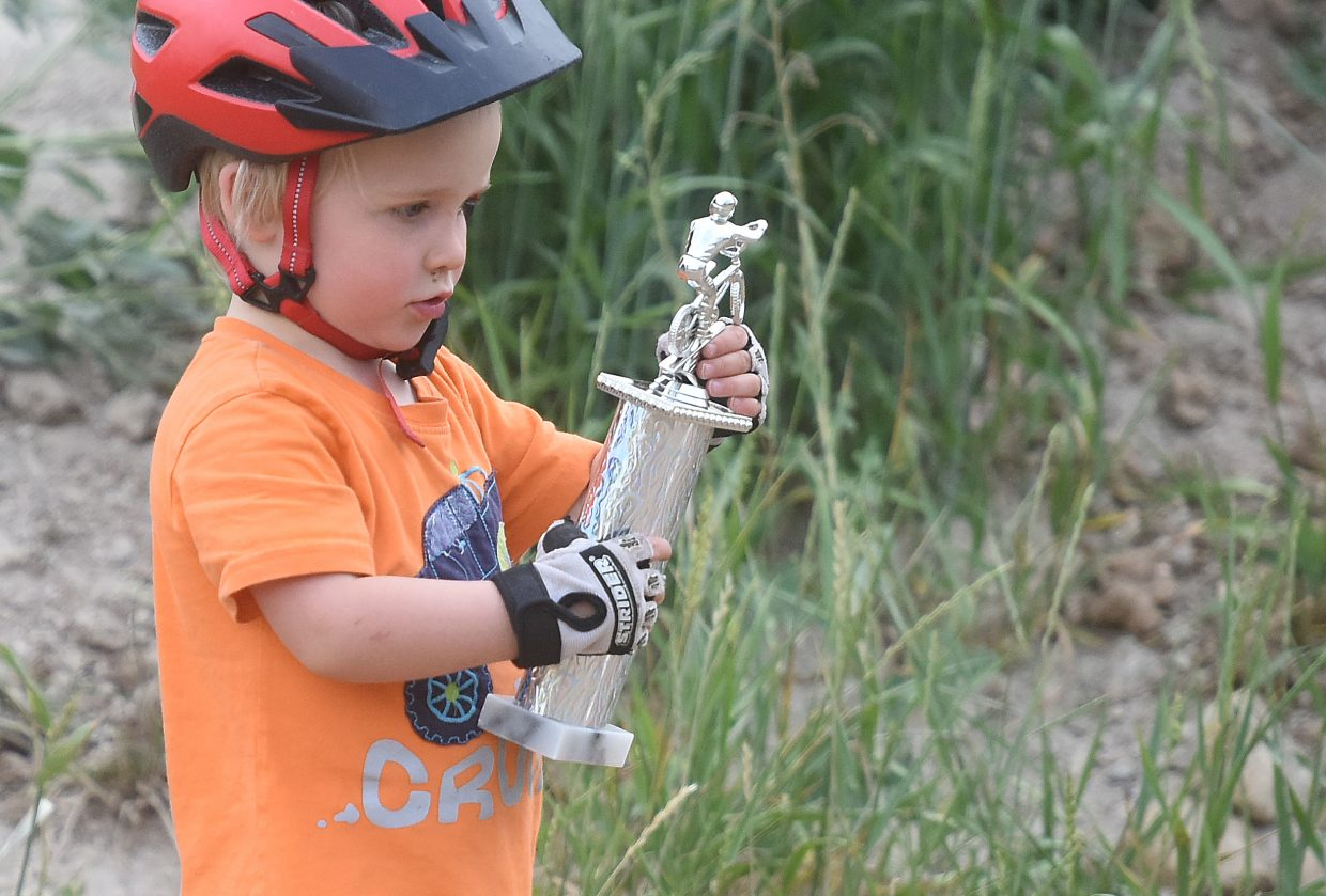 Wade McCoy gives his trophy a good examination Thursday at the Steamboat Springs BMX track.