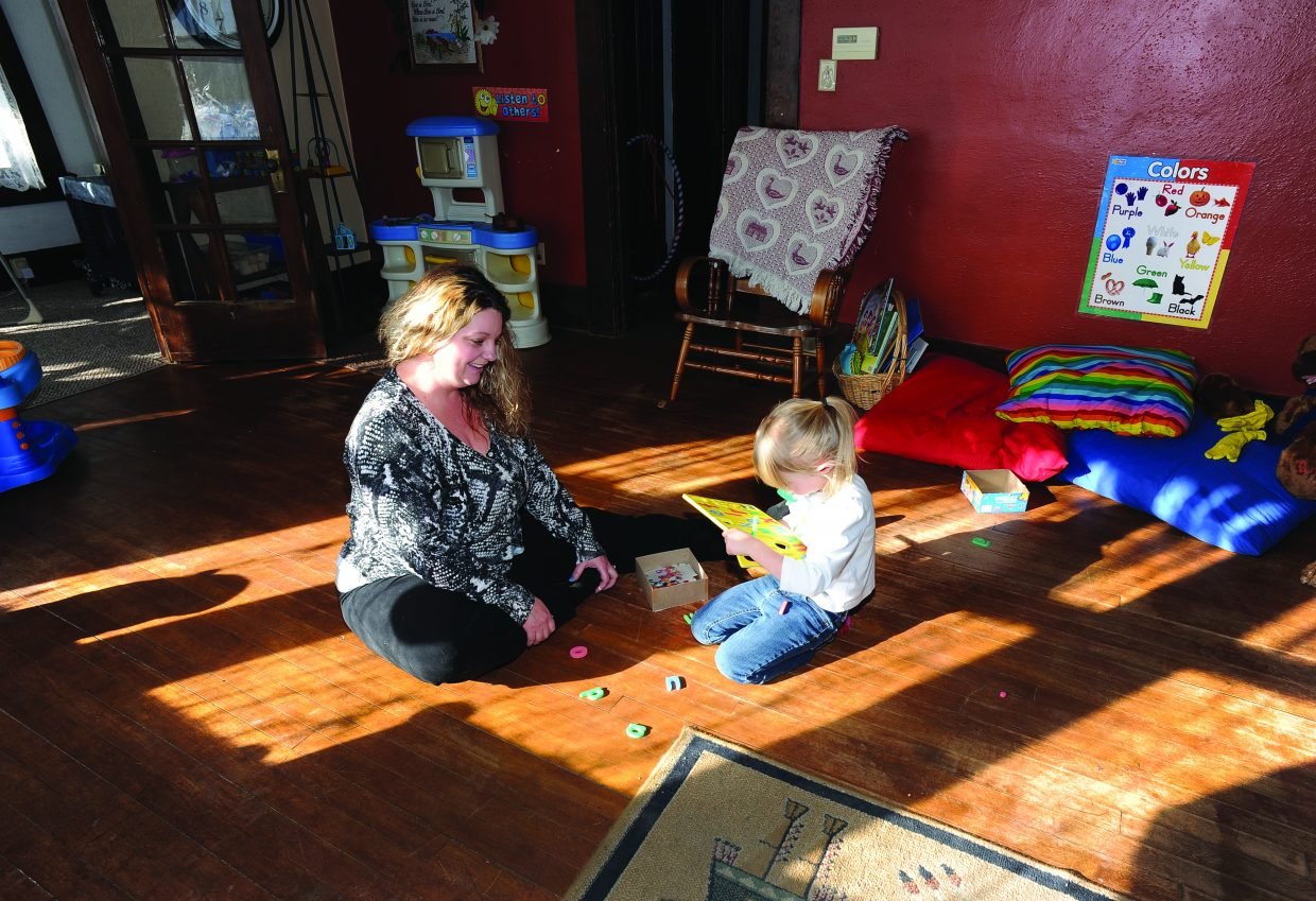 Katina Kline plays with puzzles along with 4-year-old Madison Fleeman on Thursday morning inside Katina's Wee Care Center. Katina recently opened the in-home day care center focused on taking care of toddlers.