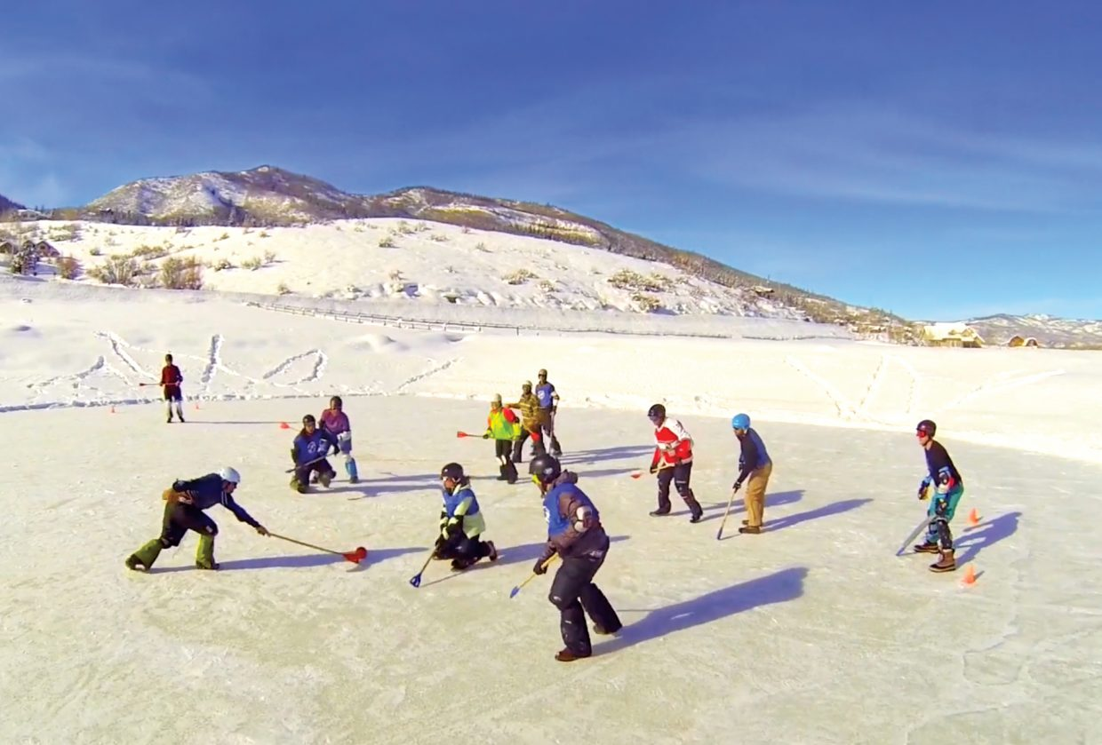 A group plays broomball in Steamboat Springs. The game is played on ice and players use brooms without bristles to knock a ball across the ice, hoping to score in the opposing team's goal.