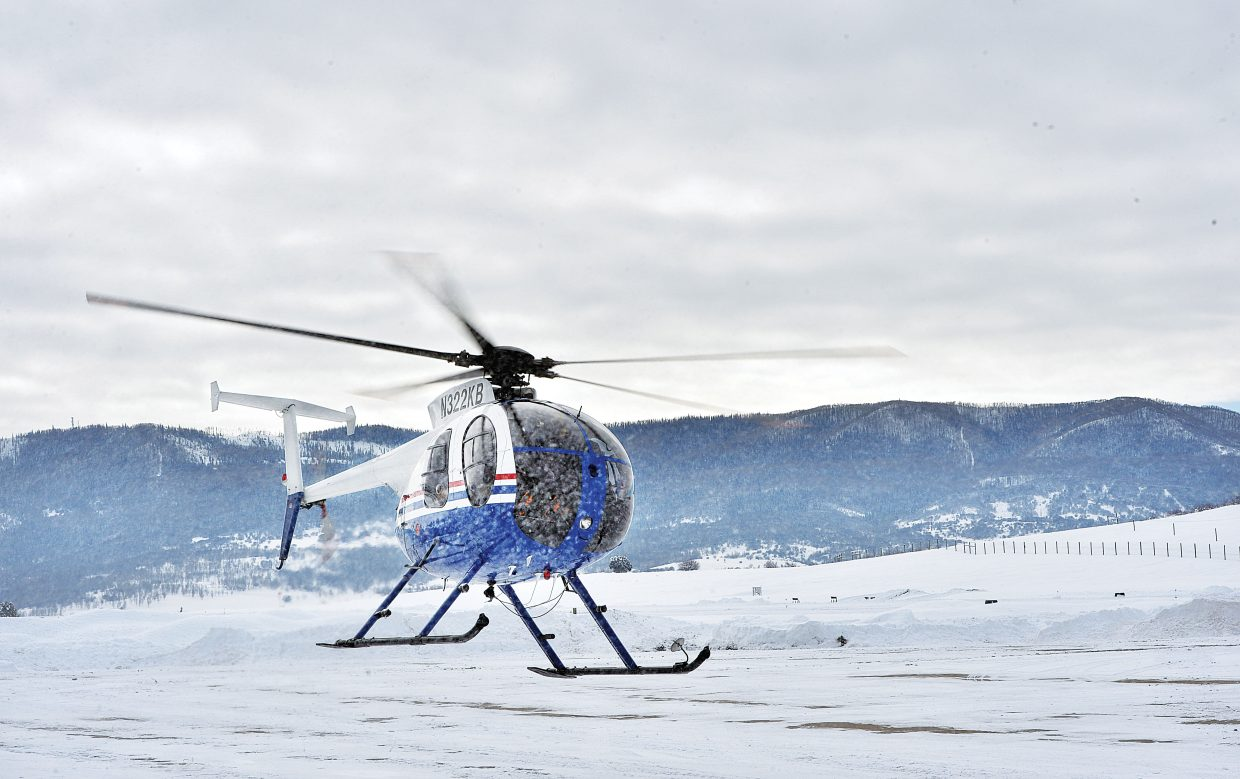 A Hughes 369D helicopter lifts off at the Steamboat Springs Airport Friday morning carrying Colorado Parks and Wildlife personnel who were working on a Big Game Winter Classification. The officials are hesitant to call it a count because they admit that there is no way to accurately count the number of animals in the field. However, they gather information about sex of the animal and the number of calves, which is run through population models to estimate the number, age and health of the big game herds in the Steamboat Springs area. Parks and Wildlife has spent the past three days surveying the area and gathering information. The classifications normally take place in the winter because herds tend to gather in low-lying areas and are easier to spot from the air.