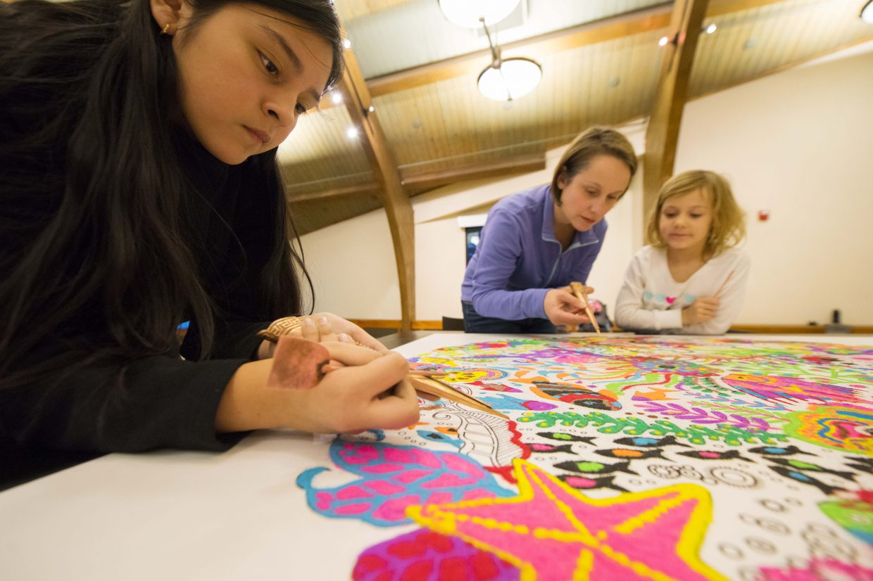 """Detail work: Yedani Mendoza Gurrola, 12, focuses on the task at hand Tuesday while working on the community sand painting project at Bud Werner Memorial Library in downtown Steamboat Springs. Peyton Bender, 6, and her mother Amy Bender work in the background, carefully scraping sand onto the design. The project ran through its first of three days on Tuesday and attracted a crowd, nearly 100 artists throughout the day. Some came and went quickly. Others, like Mendoza Gurrola, came early and stayed late. She started at noon and was still there five hours later. Why? """"I don't think my parents would let me do sand art at home,"""" she said. The project will continue from noon to 7 p.m. Wednesday and Thursday. It's free and open to the community."""