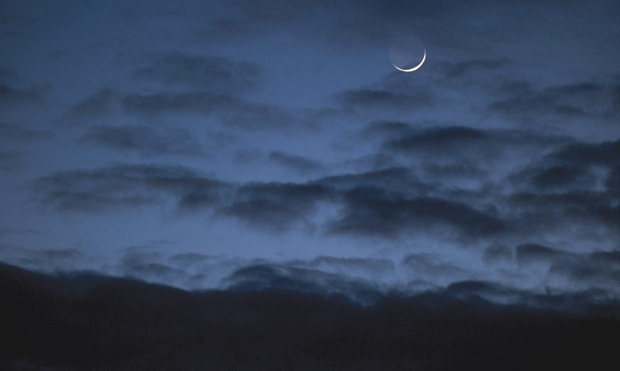 The crescent moon hangs in the early evening sky over Steamboat Springs.