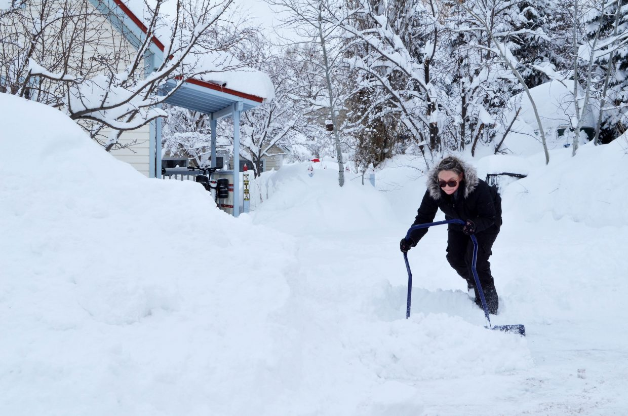 Caitlin Murphy puts some muscle into the chore of scooping more than a foot of snow out of her driveway on Pine Street in Old Town Steamboat Springs Thursday. Murphy said the storm reminded her of the Feb. 20, 2012, storm that dumped a record 27 inches on Steamboat Ski Area in 24 hours.