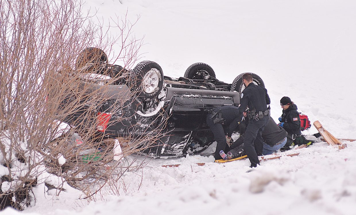 Steamboat Springs Police and members of Steamboat Fire Rescue come to the aid of an injured person involved in a one-car rollover accident just of U.S. Highway 40 near the Steamboat Campground Tuesday morning. Drivers were reporting black ice on the roads.