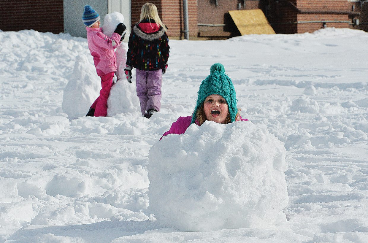 Emerald Mountain School student Mahala Wyant pushes a heavy snowball across the lawn in front of the George P. Sauer Human Services Building while building snowmen with her classmates during lunch recess Tuesday afternoon.