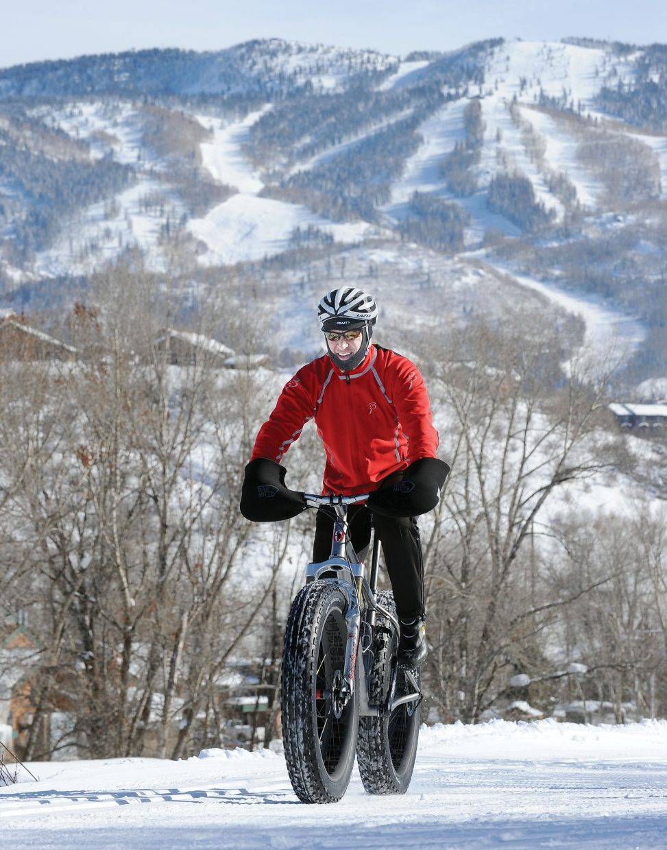 Cyclist Steve Palmquest rides a bike equipped with oversized tires on the trails at Howelsen Hill on Tuesday afternoon. The bike's tires allow it to stay on top of the snow.