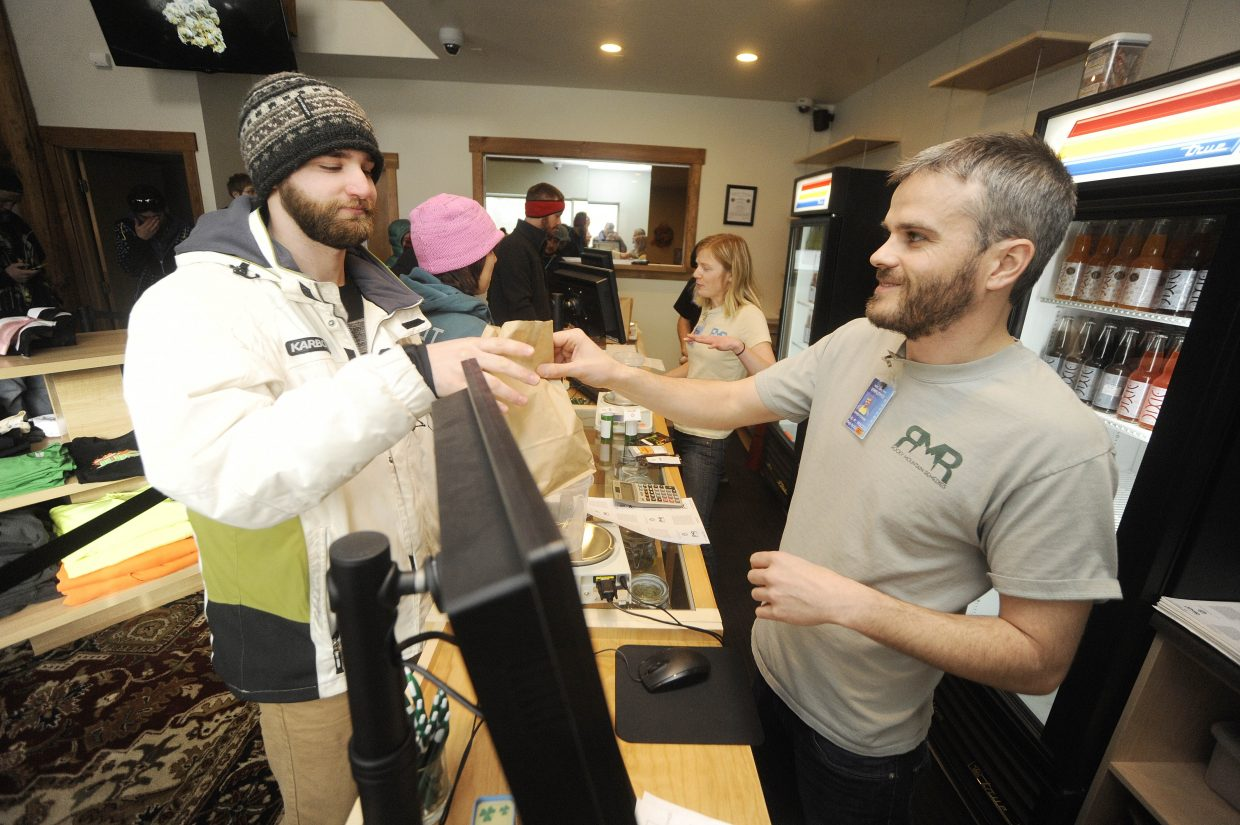 """Rocky Mountain Remedies employee Chris Fisher hands over the first legal sale of recreational marijuana to Minnesota resident Patrick Krenke on Wednesday morning. Krenke spent $112.55 and paid for it using plastic. """"That's the first time I've bought weed without cash,"""" he said."""
