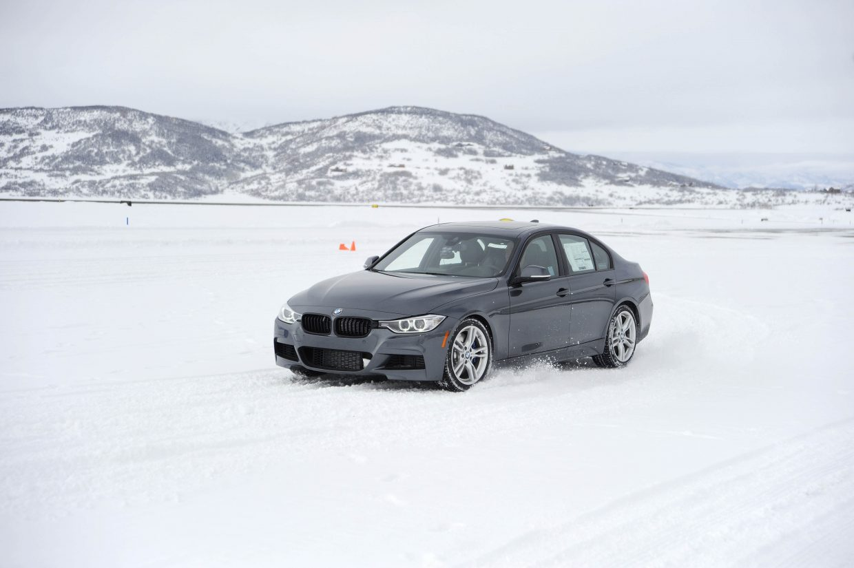 Engineer Steve Calder drives a BMW while testing new tires produced by a major tire manufacturer Friday at Steamboat Springs Airport. The company rented part of the airport parking area to perform the tests and paid to have about 140 dump truck loads of snow brought in for the track.