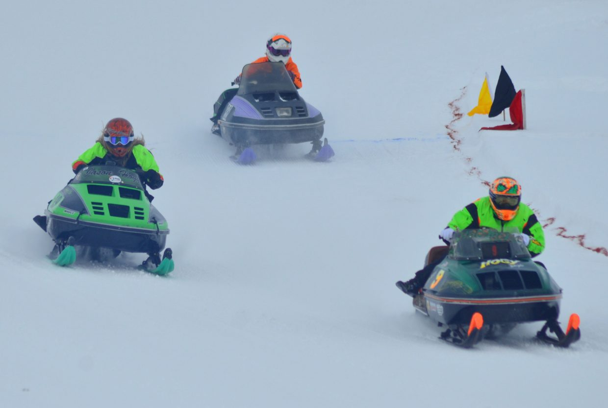 The racers of the women's segment of the Vintage & Classic Oval Snowmobile Racing Saturday round the final corner at Hayden Speedway.