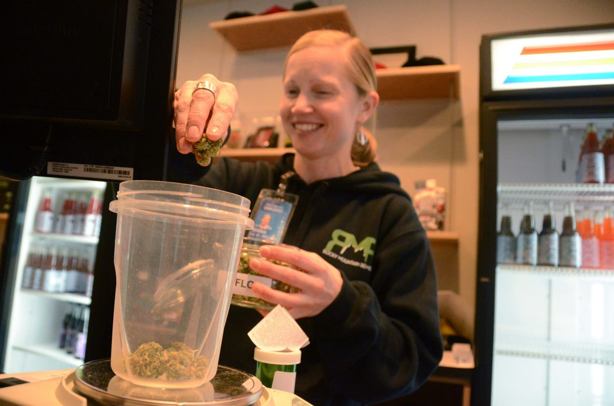 Jenna Knowles, a manager at Rocky Mountain Remedies, measures out marijuana for a Craig customer.