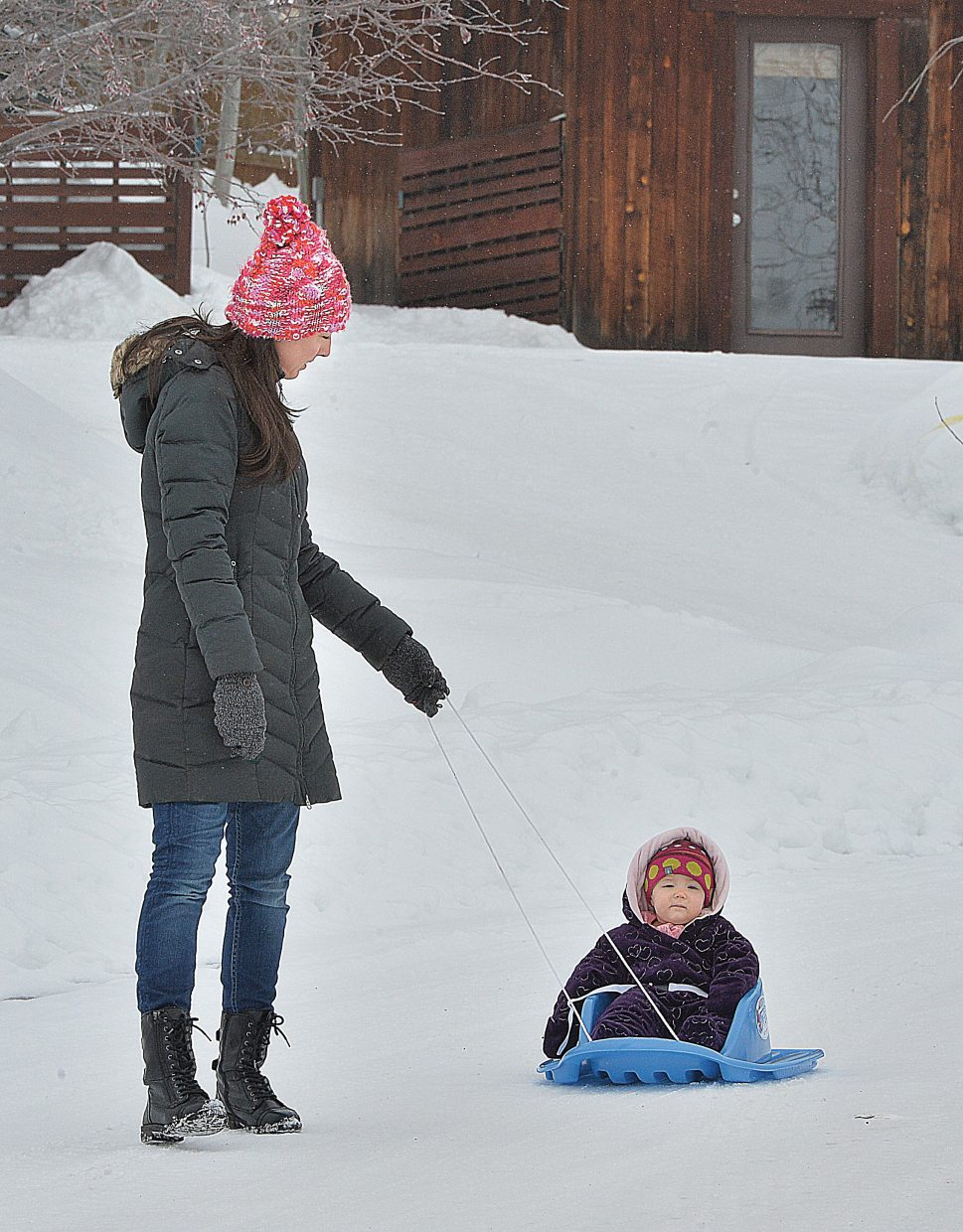 Lora Labaree and her young daughter, Aspen, didn't let the snow-packed and icy roads in the Steamboat II Subdivision stop them from getting around Friday morning. Lora simply grabbed a slid and Aspen was able to ride to the park, which is near their home.