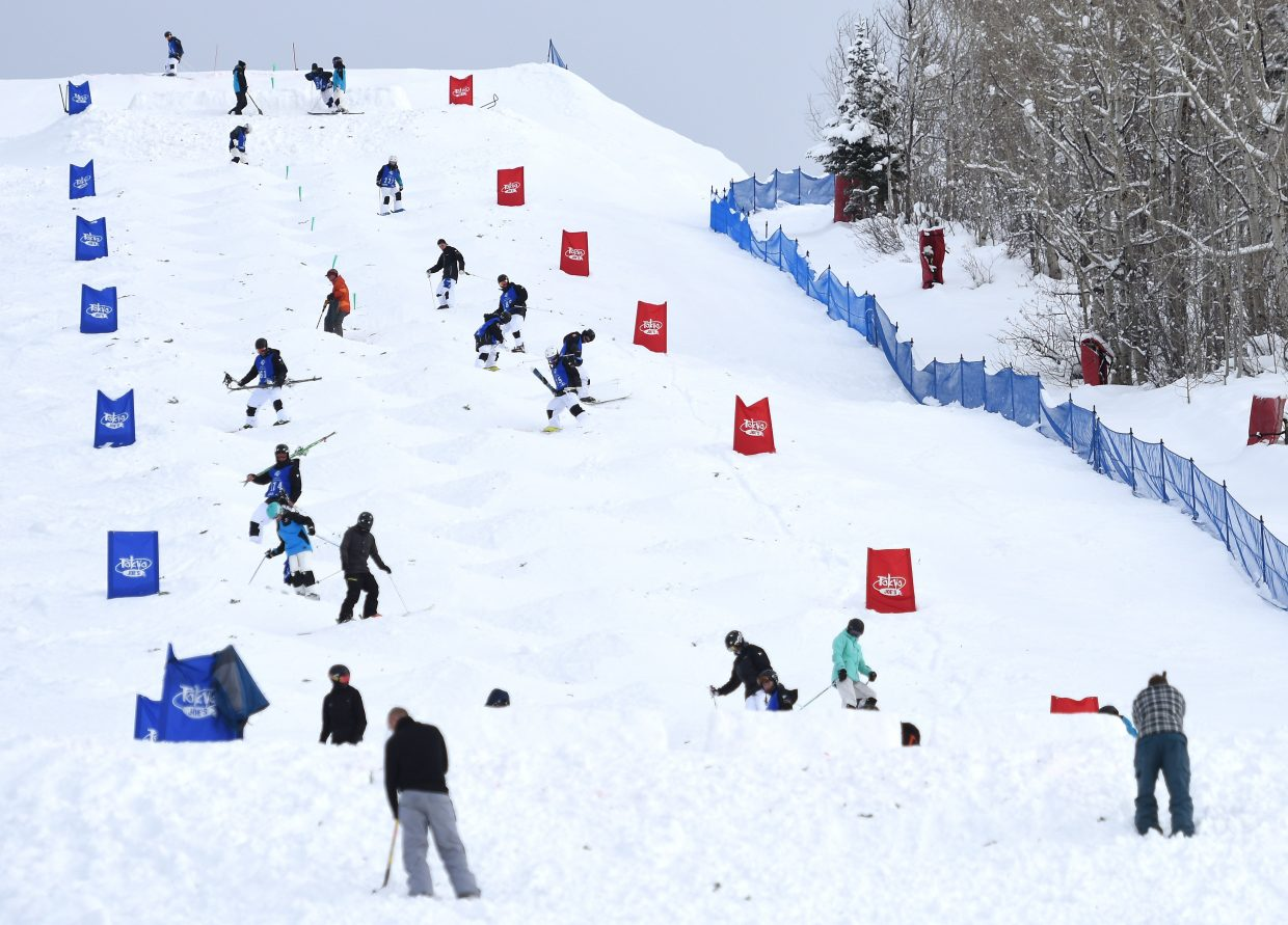 Skiers, coaches and volunteers work after Saturday's freestyle moguls competition at Steamboat Ski Area to prepare Voodoo run for Sunday's dual moguls event.