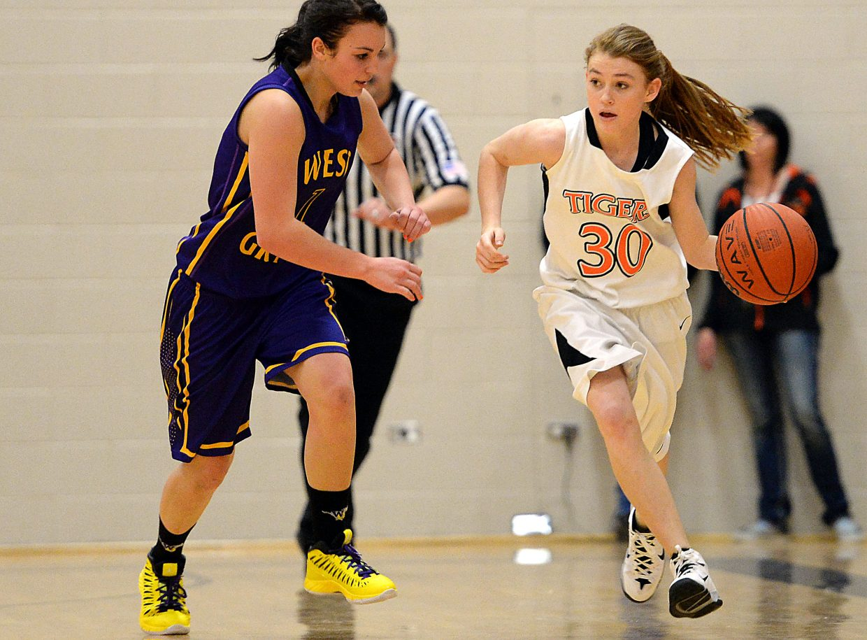 Darian Murphy brings the ball up the court through West Grand's defense Friday.