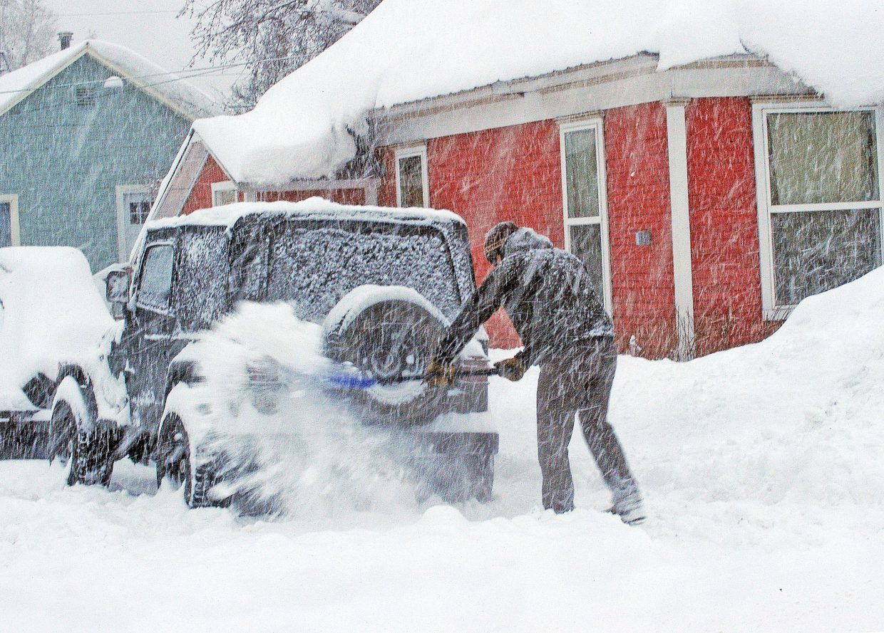Steamboat Springs resident Adam Sando shovels the snow behind his Jeep that was left from the plows during Friday's storm. The storm left several inches of snow in the downtown area, and showed no signs of letting up Friday morning.