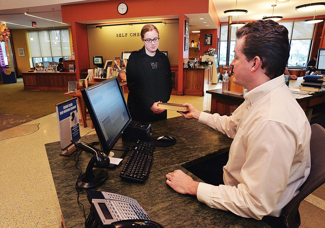 Cameron McVey checks out library card holder Keegan Rogan at the Bud Werner Memorial Library.