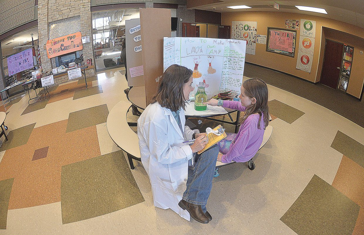 Judge Ann Henderson visits with fourth-grader Lucy Travis during the Soda Creek Elementary School Science Fair on Thursday afternoon. The students presented their projects to judges before the actual fair, which took place Thursday evening.