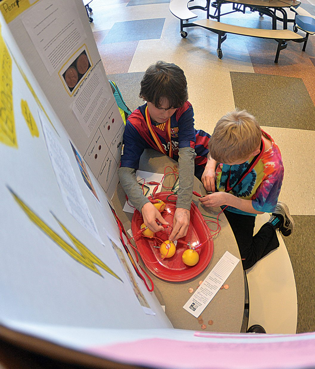 Fourth-graders Cade Gedeon, left, and Olin Webster demonstrate their project, the Lemon Battery, at the Soda Creek Elementary School's Science Fair on Thursday afternoon.