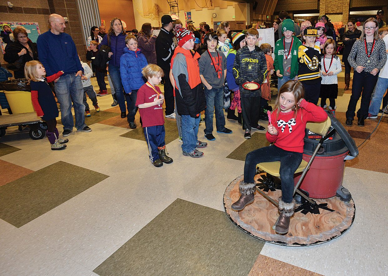 Third grader Cheyenne Williams rides on a hovercraft she built for the Soda Creek Elementary School Science Fair.