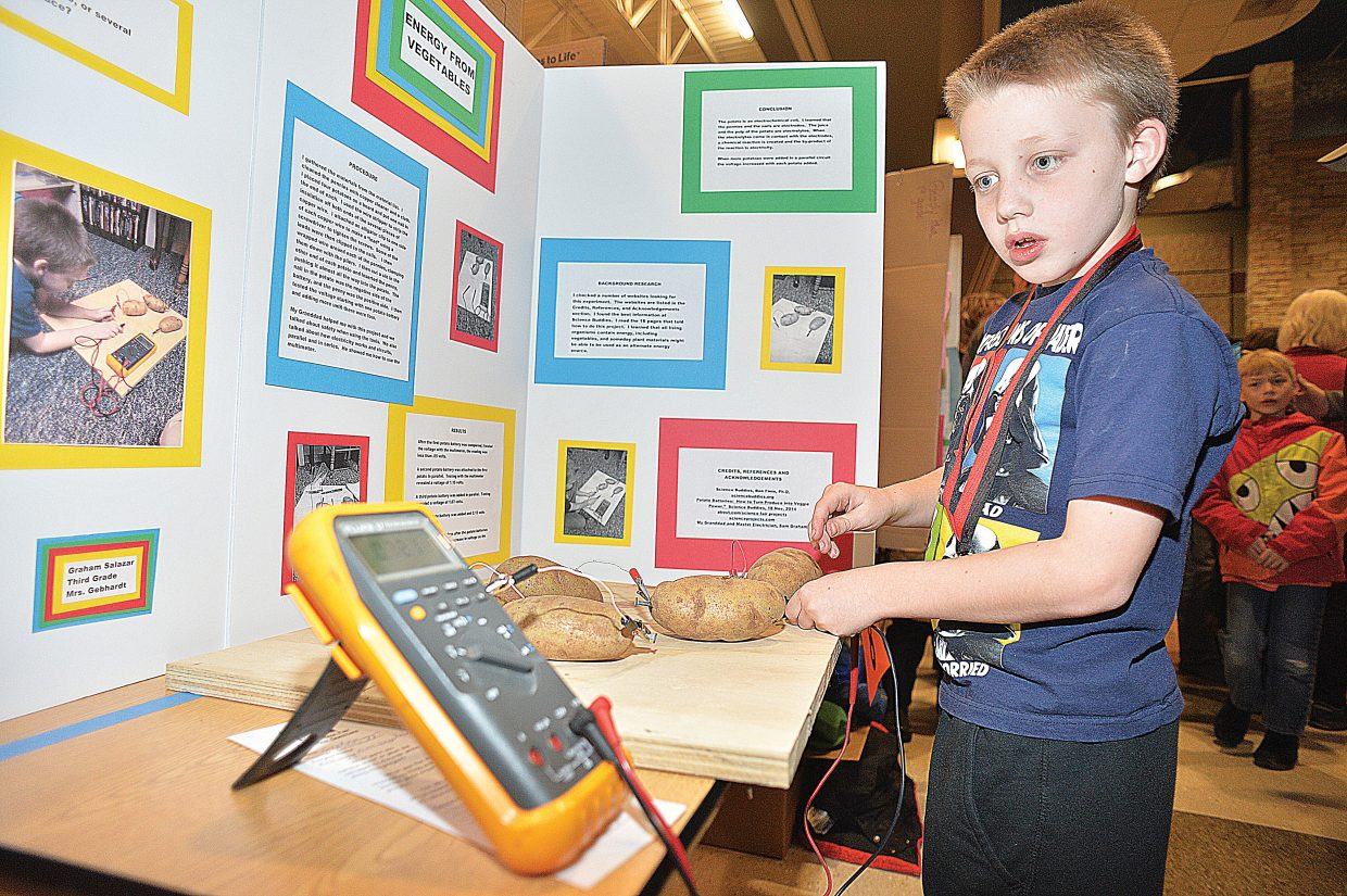 Soda Creek Elementary School third-grader Graham Salazar demonstrates his project, which uses potatoes to produce electricity. The Science Fair drew a large crowd Thursday night and featured tons of young scientists eager to demonstrate what they have learned.