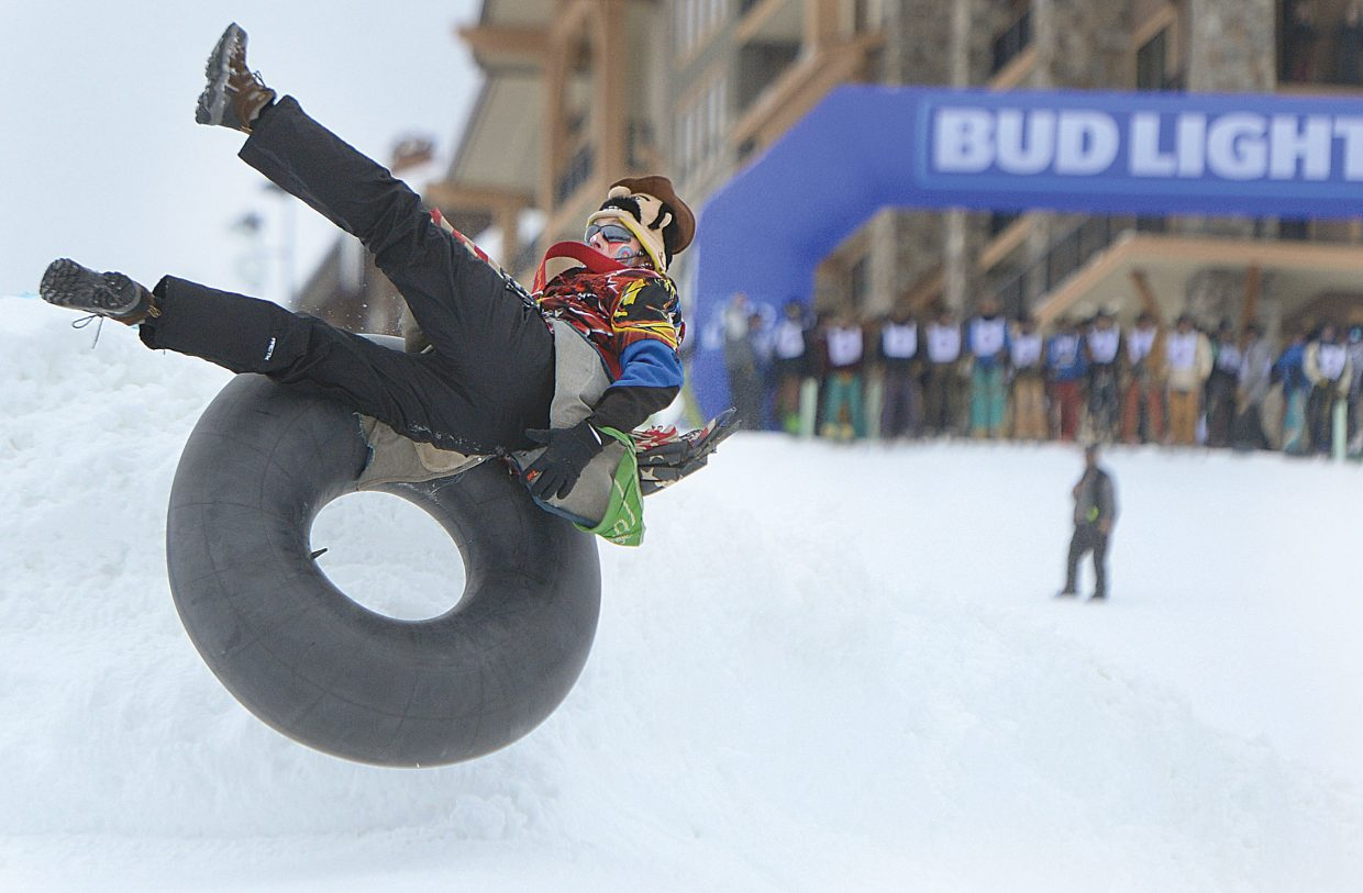 Rodeo clown J.W. Winklepleck launches off the jump on an inner tube prior to the start of the cowboy stampede — the final race of the 43rd Bud Light Cowboy Downhill, which was held on the slopes of Steamboat Ski Area Monday afternoon.