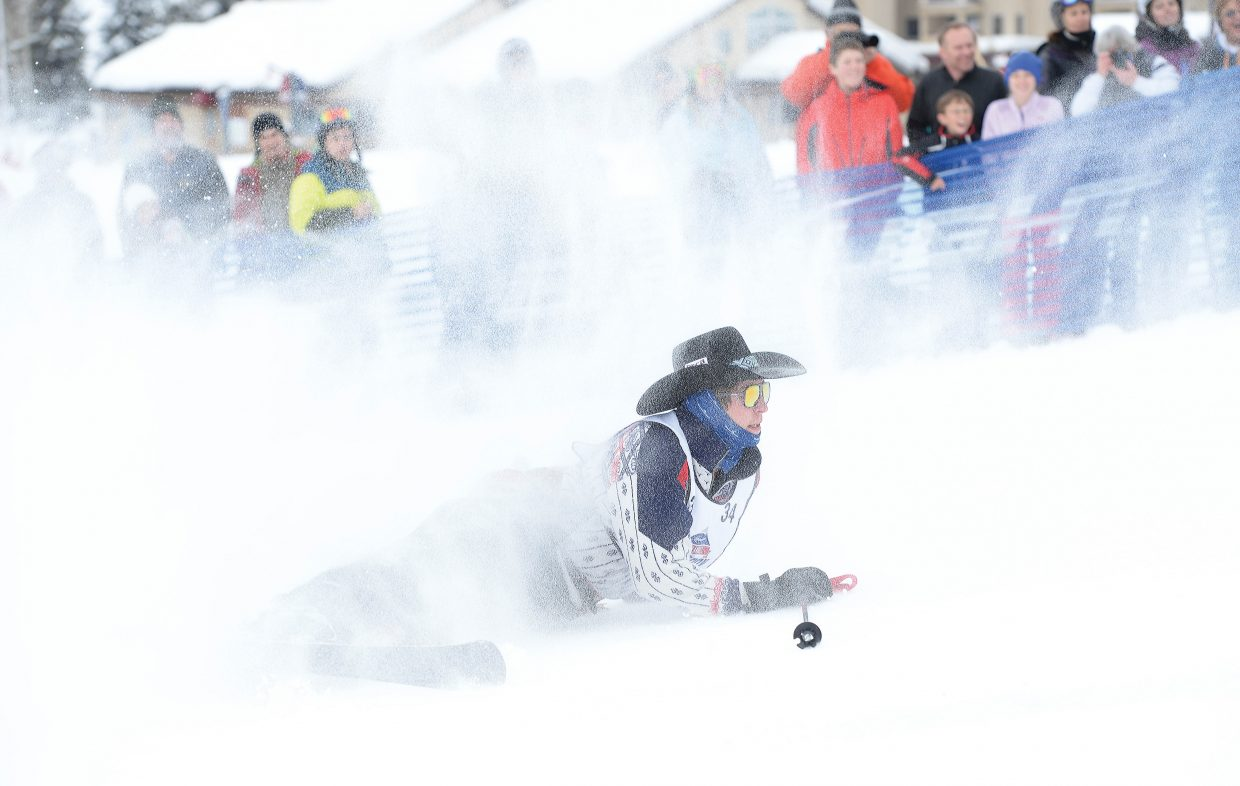 The air surrounding florescent cowboy Dillon Snare was filled with snow after he crashed during the 42nd annual Bud Light Cowboy Downhill at the base of Steamboat Ski Area Monday afternoon. The long-running Steamboat Springs tradition attracts cowboys from the National Western Stock Show in Denver. They come to Steamboat to compete in a head-to-head race where they must navigate through a slalom course, over a jump and then lasso a cowgirl and saddle a horse before crossing the finish line.