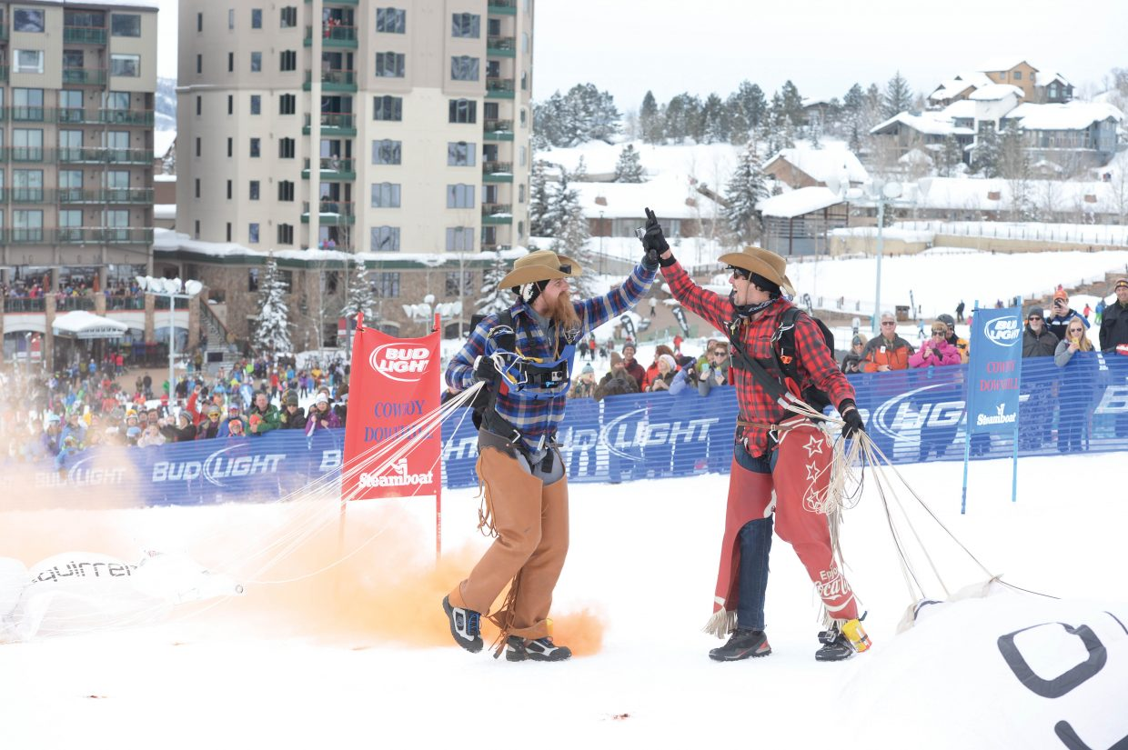 Neil Amonson, left, and Jesse Hall share a high-five after the GoPro Bomb Squad members landed a successful jump at the 42nd annual Bud Light Cowboy Downhill at the base of Steamboat Ski Area Monday afternoon. The GoPro Bomb Squad members opened the long-running Steamboat Springs tradition that attracts cowboys from the National Western Stock Show in Denver.
