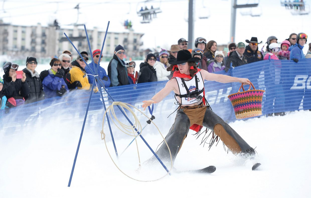 Jacob Crawley, a bronc rider from Texas, reaches for his lasso at the bottom of his ski run during the 42nd annual Bud Light Cowboy Downhill at the base of Steamboat Ski Area Monday afternoon. Crawley dressed up as Little Red Robin Hood, and his brother, and opponent, dressed up like the Big Bad Wolf.