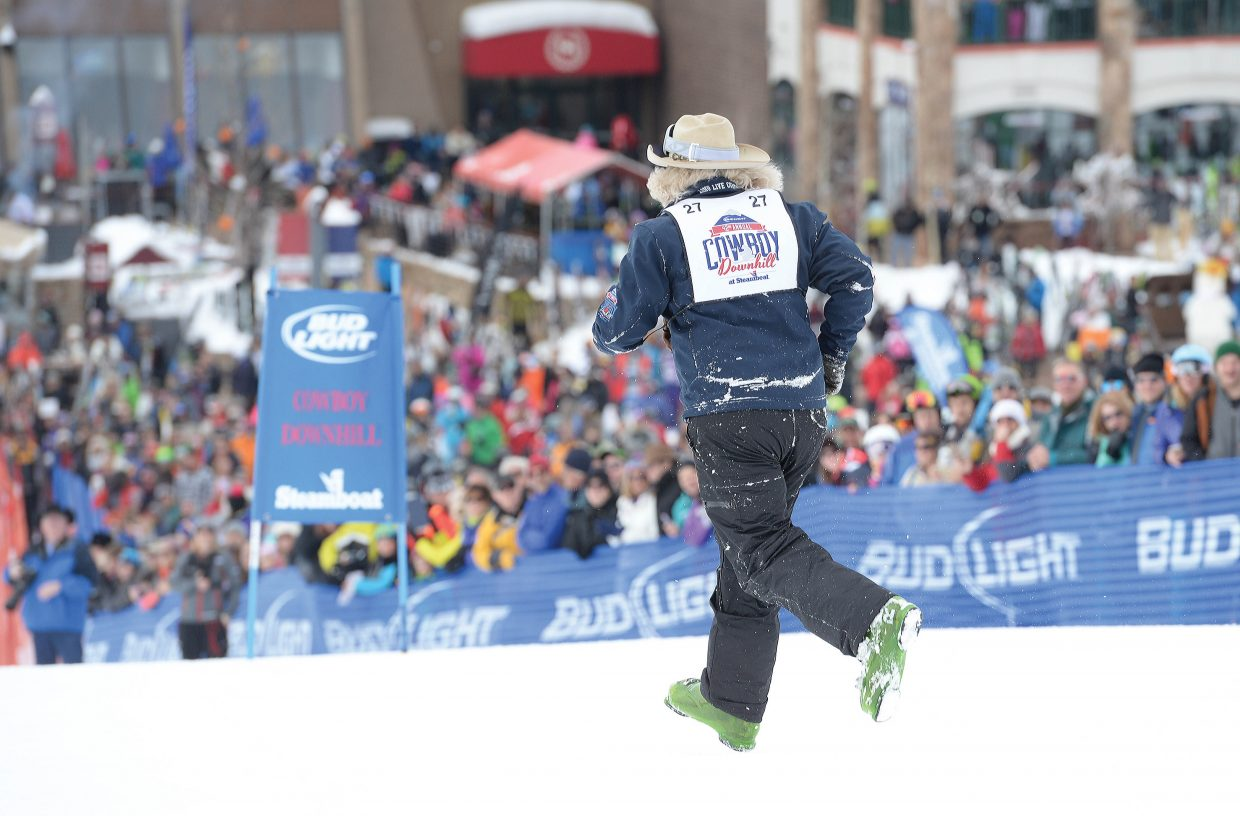 After losing his skis in a crash, Texas bareback rider Bob Logue runs through the course toward the finish line of the 42nd annual Bud Light Cowboy Downhill at the base of Steamboat Ski Area Monday afternoon. As Logue proved, skis were optional at times for the visiting cowboys.