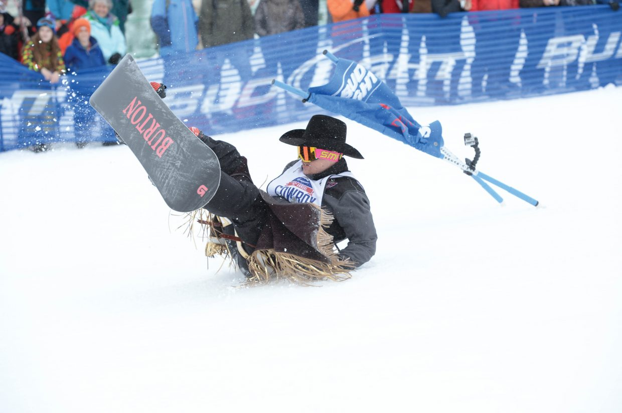 Tanner Aus, a bareback rider from Minnesota, crashes into a gate during the 42nd annual Bud Light Cowboy Downhill at the base of Steamboat Ski Area Monday afternoon.