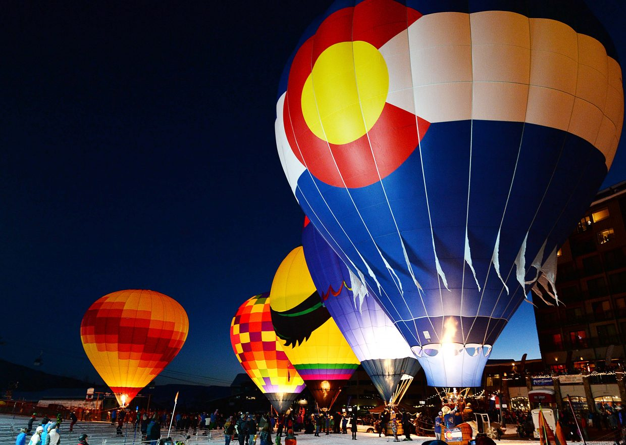 Revelers watch as hot air balloons light up the night at the base of Steamboat Ski Area.