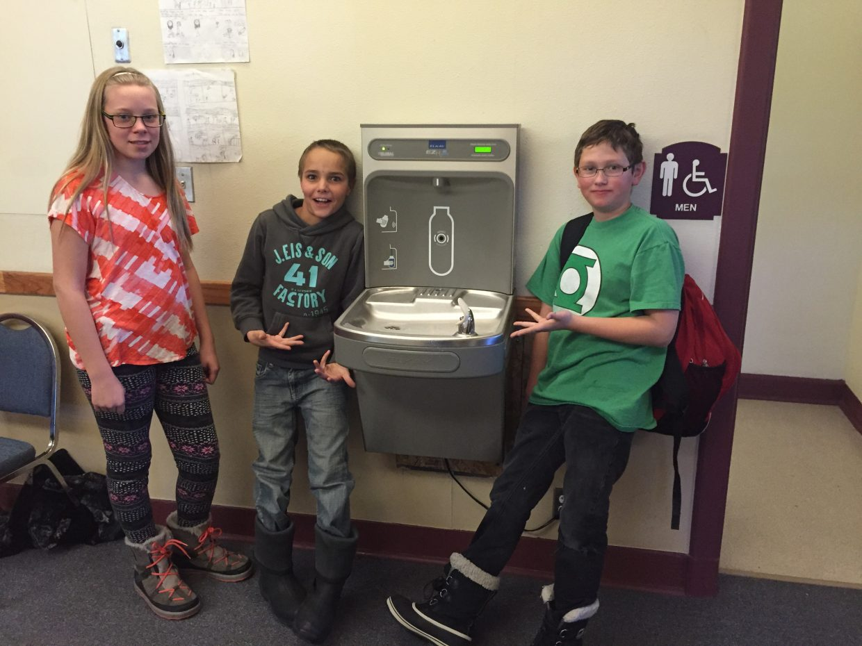 Soroco Middle School seventh-graders Leona Thurston, Gene Bracegirdle and Jonah Marshall stand near a water bottle filling station installed at the school in the fall. The district is raising money to install another station at Soroco High School.