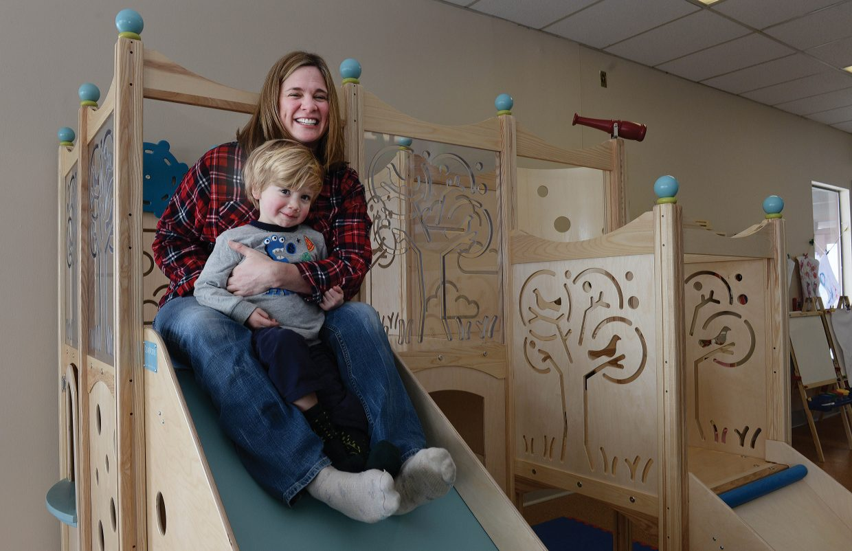 Charlotte Harriman and her son, Caleb, play on the slide at the new Kids Playgarden, a drop-in day care center located in Sundance at Fish Creek.