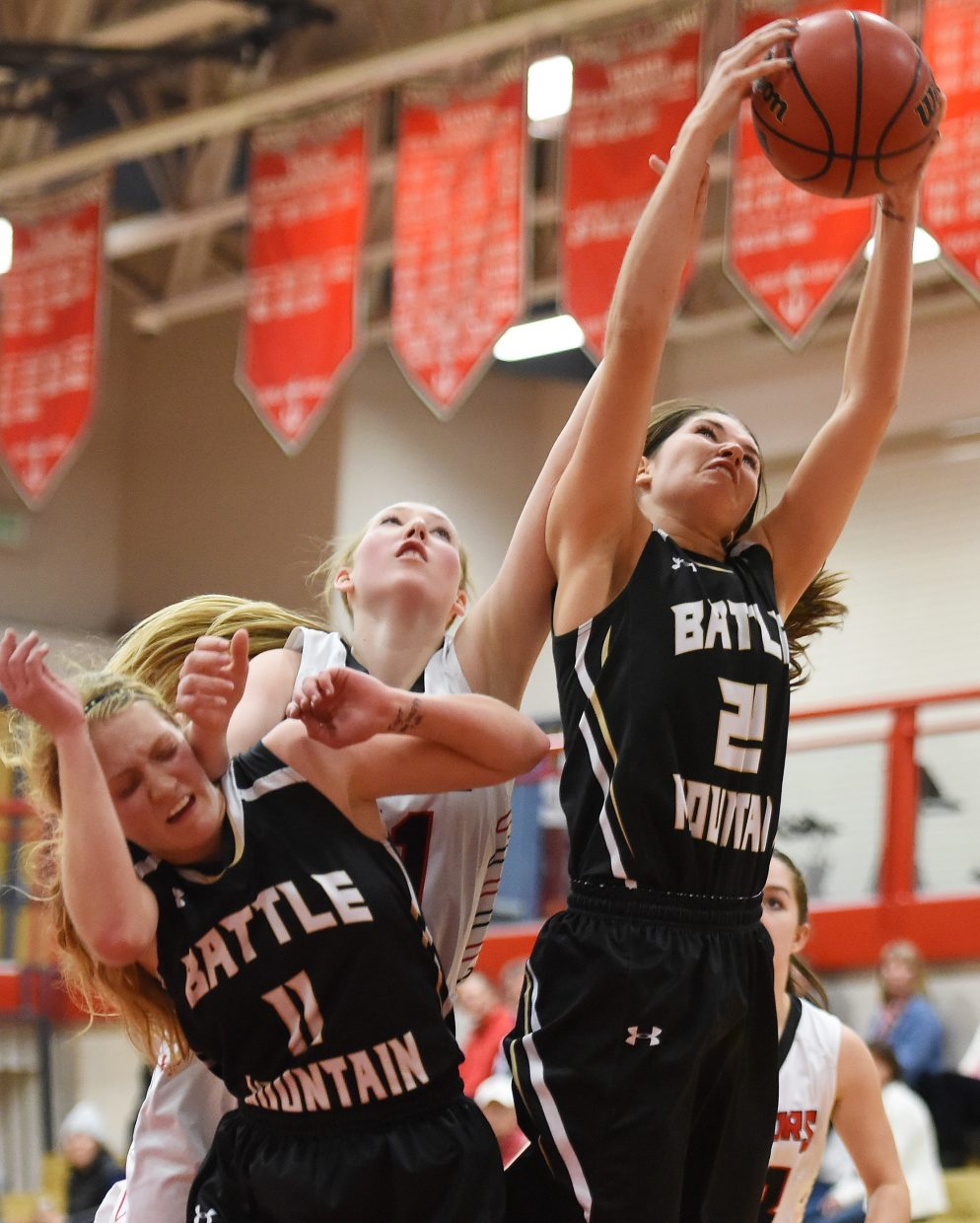 Steamboat's Ellie Crouch crashes through a pair of Battle Mountain players as she reaches for a rebound Tuesday.