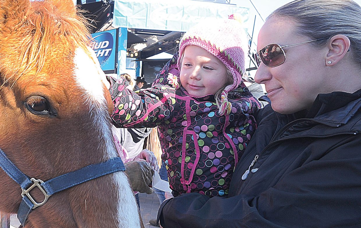 Ellis Whitcher and her mom Lindsey visit with some of the horses at the base of the Steamboat Ski Area prior to the start of Monday's 40th annual Bud Light Cowboy Downhill.