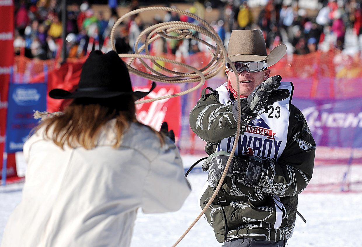 Tate Stratton, of Oklahoma, ropes a Steamboat Ski Area employee as part of the 40th annual Bud Light Cowboy Downhill Monday at the base of Steamboat Ski Area.