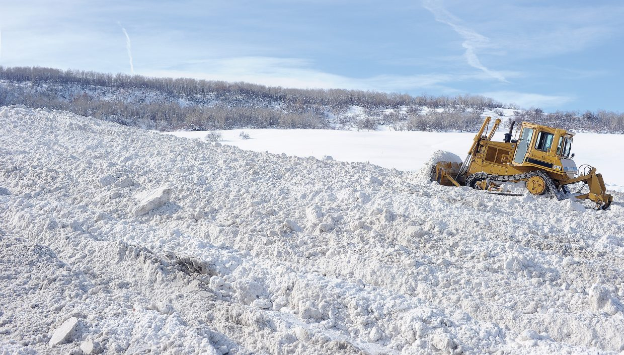 Eric Heintz, with the City of Steamboat Springs street department, uses a bulldozer to spread snow from last week's storms in a storage area behind the city shops.