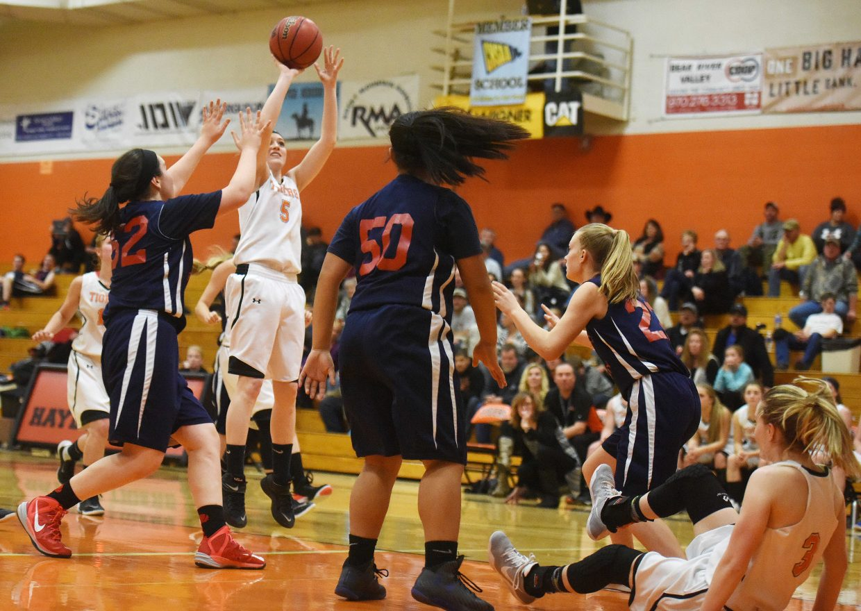 Hayden senior Darian Murphy pulls up for a shot after a falling-down pass from Grace Wilkie, right, on Friday as the Tigers ran it up on Caprock Academy.
