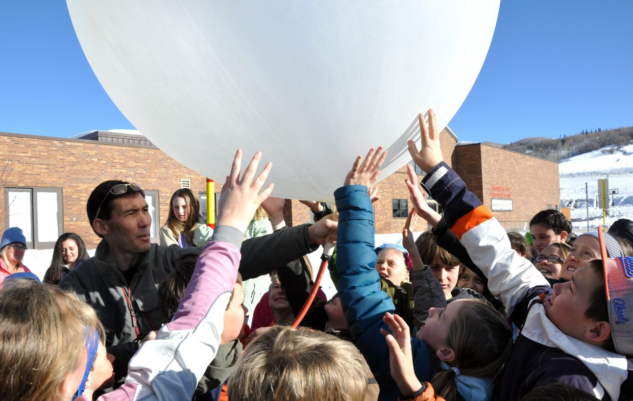 Tim Lim, an engineer with the National Center for Atmospheric Research, holds a weather balloon Wednesday as Strawberry Park Elementary School students reach in to touch it.