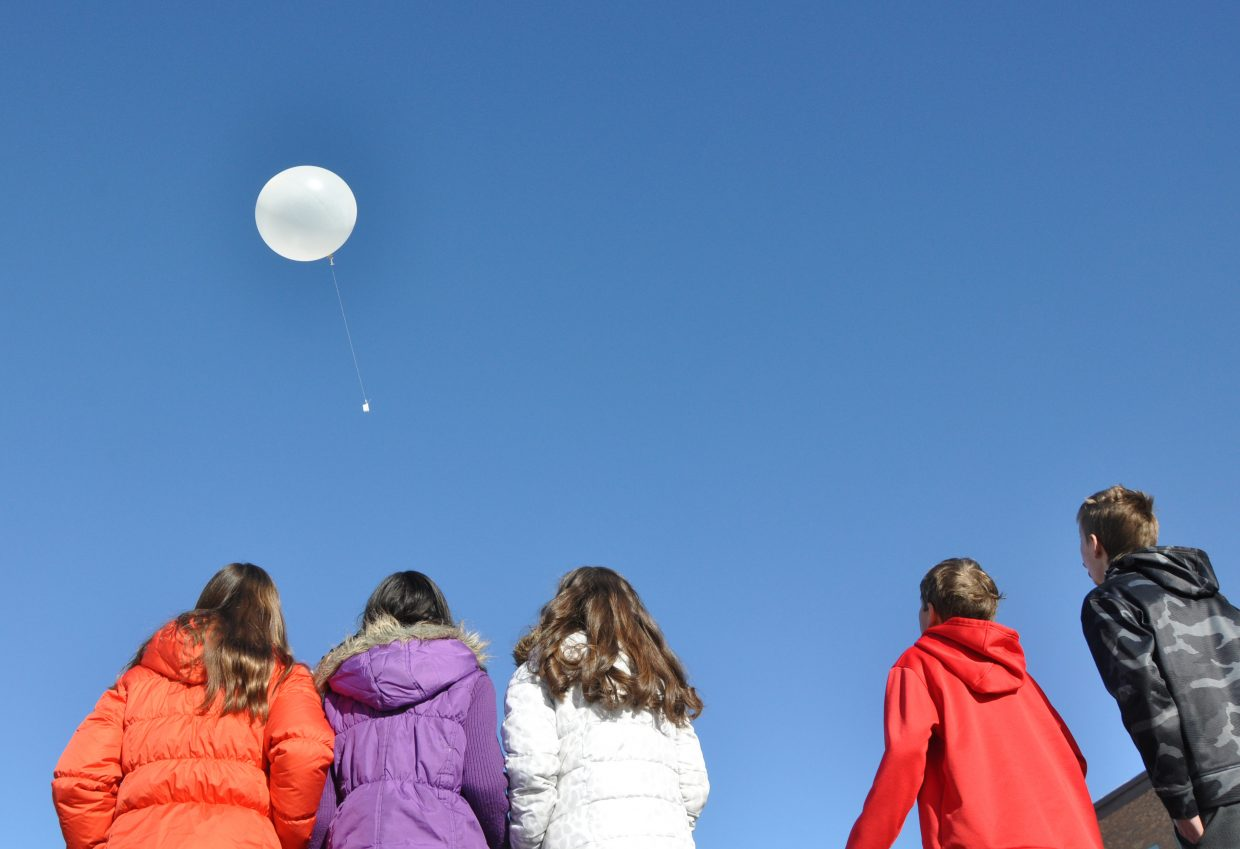 Strawberry Park Elementary School students watch a weather balloon float away Wednesday. The radiosonde attached to the balloon collects weather data.